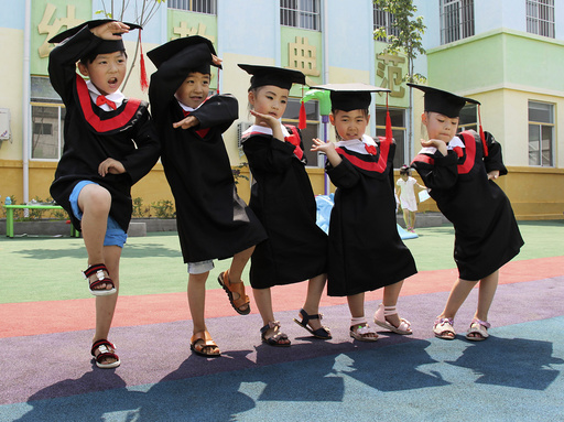 Children in gowns and mortarboards pose for pictures during their kindergarten graduation ceremony, in Wenxian county