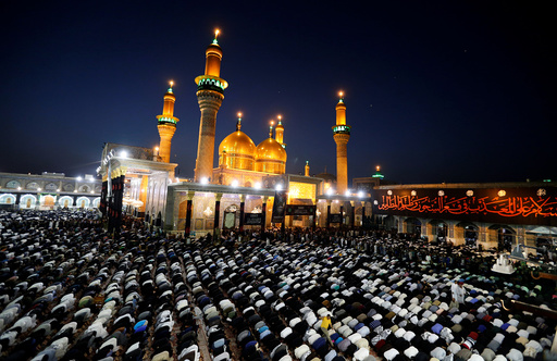 Shi'ite pilgrims pray at the Shrine of Imam Moussa al-Kadhim in Baghdad