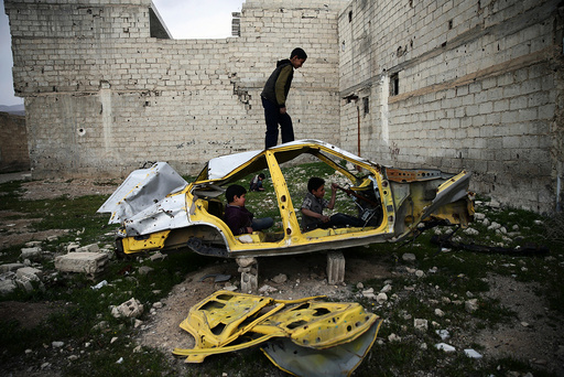 Boys play on a wrecked car in the rebel held besieged Douma neighbourhood of Damascus