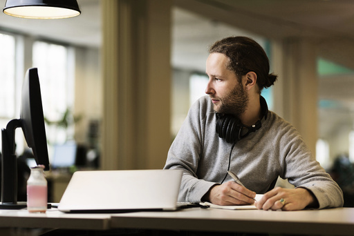 Businessman writing while using desktop PC in creative office