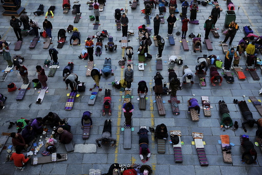 Pilgrims pray outside the Jokhang Temple in central Lhasa, Tibet Autonomous Region, China, at dawn