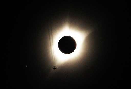 A jet plane flies by the total solar eclipse in Guernsey