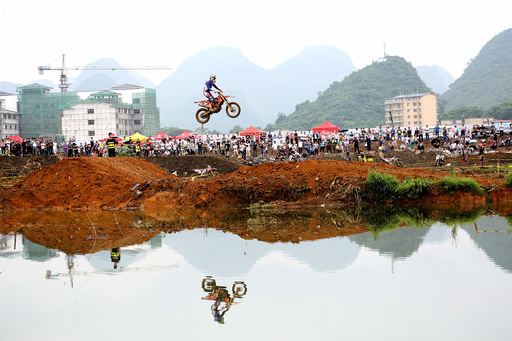 A rider rides a motorcycle in the air during a competition at Guilin
