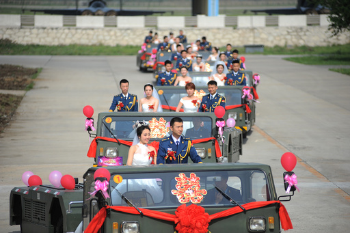 Soldiers of China's Liberation Army (PLA) air force stand on military vehicles as they attend a group wedding in Anshan