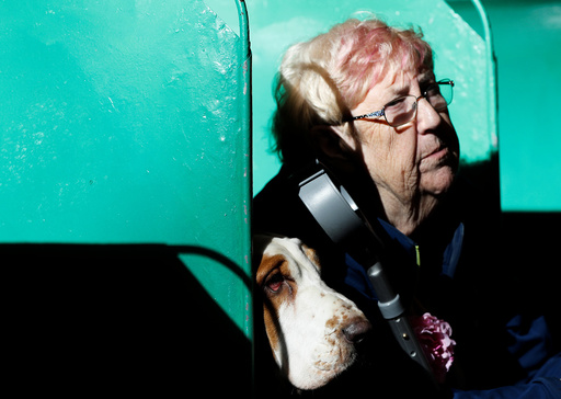 A woman sits with her Basset Hound during the first day of the Crufts Dog Show in Birmingham
