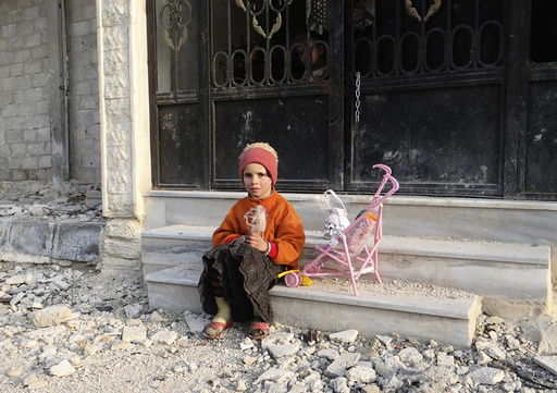 A girl carrying a doll sits on a step of a building as a boy peeks out from its gate in the Damascus suburbs of Arbeen