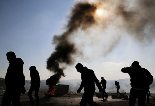 Palestinian protesters react to teargas fired by Israeli troops during clashes in the West Bank village of Silwad, near Ramallah