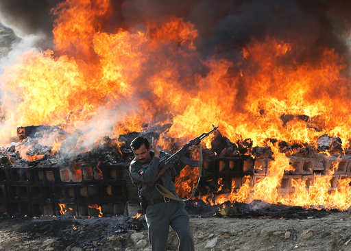 An Afghan officer reacts in front of a burning pile of seized narcotics and alcoholic drinks, in the outskirts of Kabul