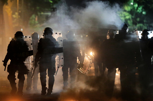 Riot policemen walk past a barricade on fire after a clash with ant-government demonstrators during a protest against Brazilian social welfare reform project, in Rio de Janeiro