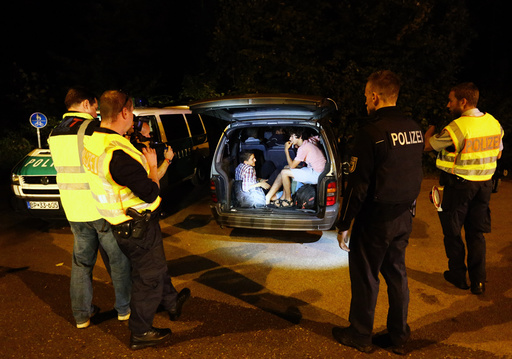 A group of migrants from Syria sits inside a vehicle stopped by German police on a country road heading to Freilassing, Germany from Salzburg