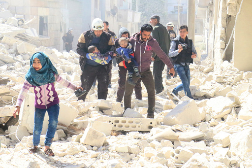 People and a civil defence personnel carry children at a damaged site after an air strike on rebel-held Idlib city