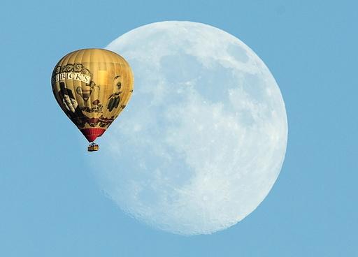 A hot air ballon floats past a rising moon over Rancho Santa Fe, California