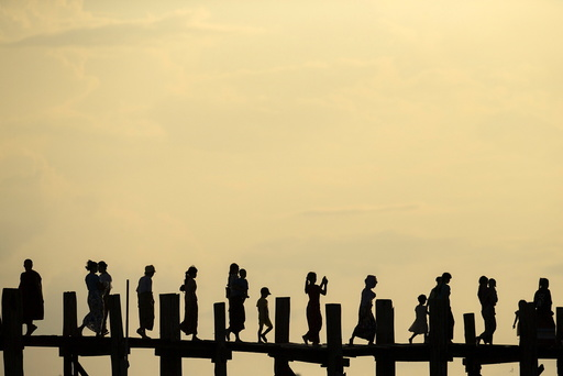 People cross U Bein bridge over Tuangthaman Lake in Mandalay, Myanmar