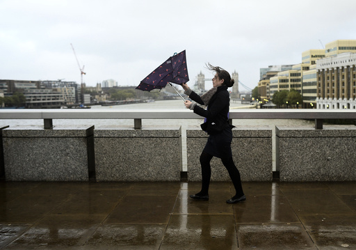 A commuter loses control of her umbrella as she braves the wind and rain while crossing London Bridge in London