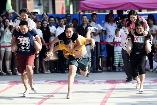 A couple fall as they take part in a high-heels race in Taiyuan