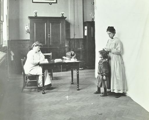 School nurse examining girls' hair for head lice, Chaucer School, London, 1911. Artist: Unknown.