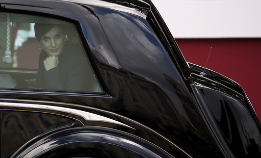 Spanish Queen Letizia leans on the window as she leaves with Spanish King Felipe after a military parade marking Spain's National Day in Madrid