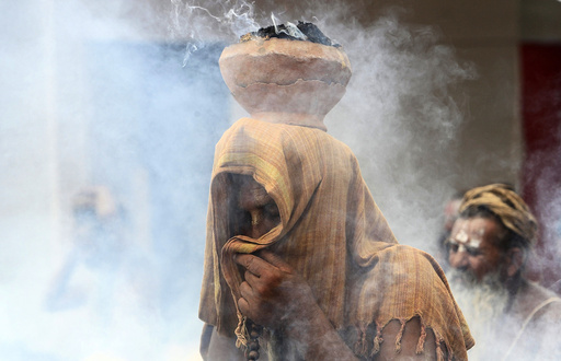 A Sadhu covers his face as an earthen pot with burning Upale rests on his head during a prayer ceremony at the Simhastha Kumbh Mela in Ujjain