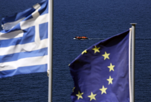 A dinghy overcrowded by migrants and refugees approaches the island of Lesbos as Greek and EU flags flutter atop a hill