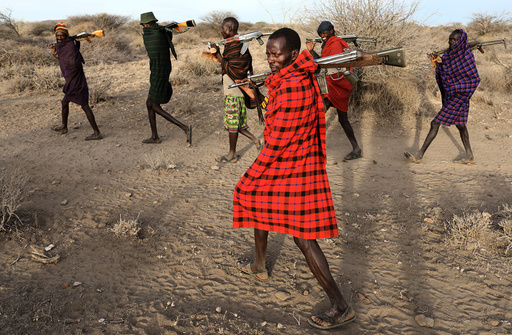 Turkana tribesmen walk with guns in order to protect their cattle from rival Pokot and Sambur tribesmen near Baragoy