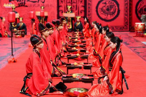 Couples attend a group wedding ceremony in traditional Han Dynasty style as they celebrate Qixi festival, or Chinese Valentine's Day, in Hengyang