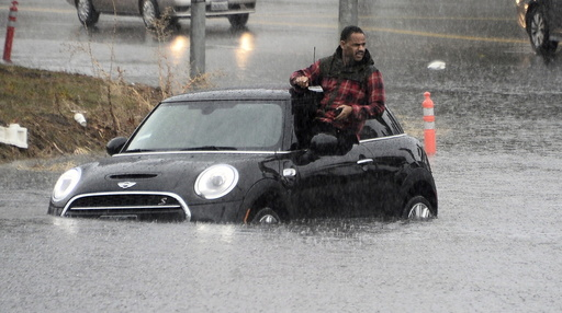 A driver climbs out of a window of his car after driving onto a flooded road in Van Nuys