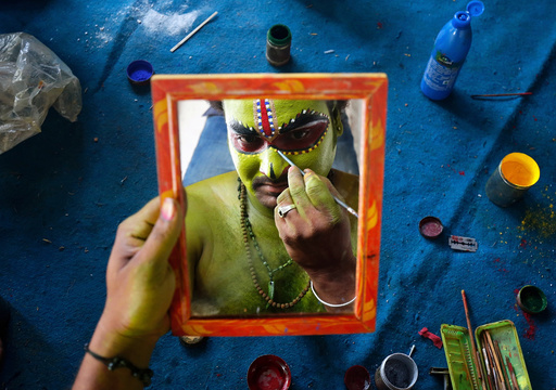An artiste is reflected in a mirror as he applies make-up backstage before taking part in a celebration to mark Hindu festival of Ramnavami inside the premises of a temple in Bengaluru
