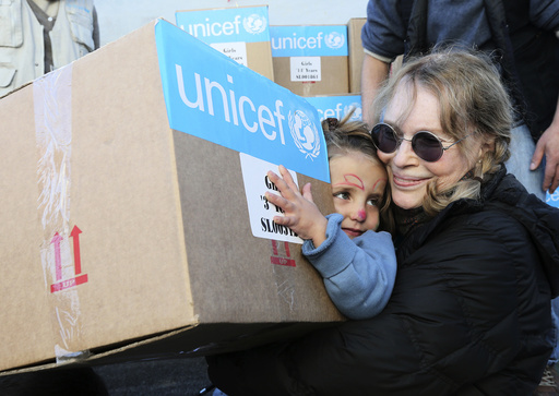 U.S. actress Mia Farrow, a UNICEF goodwill ambassador, distributes aid to Syrian refugee children in Baalbeck, Bekaa valley