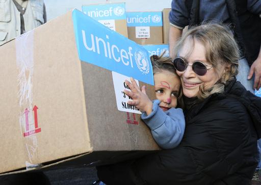 U.S. actress Mia Farrow, a UNICEF goodwill ambassador, distributes aid to Syrian refugee children in Baalbeck, Bekaa valley