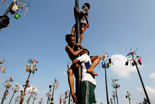 Participants climb greased poles to collect prizes during a Panjat Pinang event organised in celebration of Indonesia's 71st Independence day in Jakarta, Indonesia