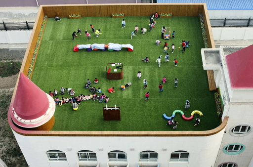 Teachers and students exercise on the playground located on the roof of a kindergarten building, in Xi'an