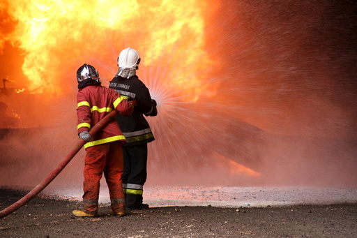 Firefighters try to put out the fire in an oil tank in the port of Es Sider, in Ras Lanuf