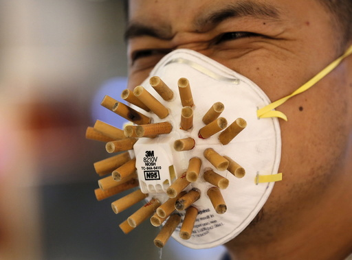 Man wears a mask decorated with cigarette butts, designed by Chinese designer Wen Fang at Wen's