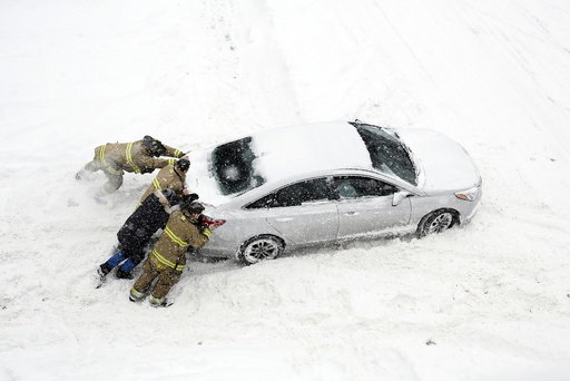 Firefighters help push a car stuck in snow during a winter storm in Ottawa