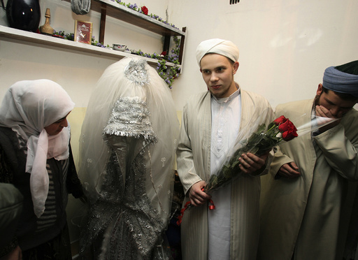 Russian citizen Abdul Rakhim and his bride Nasebakhon stand with witnesses at a wedding in Dushanbe
