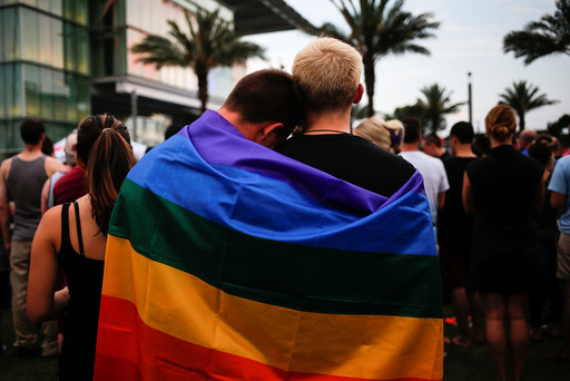 Man draped in rainbow flag embrace ahead of candle light vigil for victims of mass shooting in Orlando, Florida