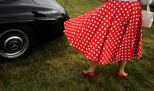 A woman arrives at the annual Goodwood Revival historic motor racing festival, celebrating a mid-twentieth century heyday of the racing circuit, near Chichester in south England