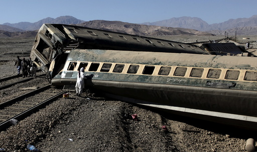 A passenger looks for his belongings after a train derailed in Quetta