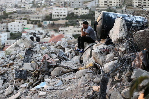 A Palestinian man sits atop the rubble of a house which was destroyed by Israeli troops during an Israeli raid in the West Bank city of Jenin