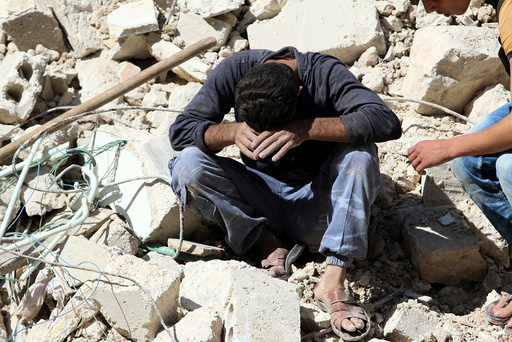 A man reacts on the rubble of damaged buildings after losing relatives to an airstrike in the besieged rebel-held al-Qaterji neighbourhood of Aleppo