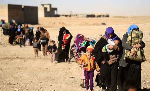 Displaced people fleeing from Islamic State militants in Tahrir neighborhood, walk in Mosul