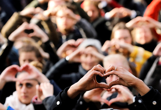 People make hearts with their fingers during a ceremony outside the Bourse, commemorating the first anniversary of the bomb attacks in Brussels metro and the Belgian international airport of Zaventem, in Brussels