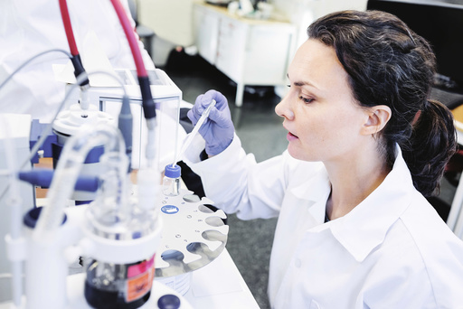 Female scientist using pipette in laboratory