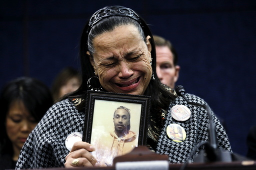 Miyoshia Bailey of Chicago struggles to speak while holding a photo of her slain son Cortez, during a press conference on gun violence in the U.S. Capitol in Washington