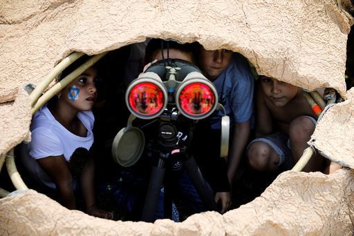 Israeli children look through binoculars during a display of Israeli Defense Forces equipment and abilities, as part of the celebrations for Israel's Independence Day marking the 69th anniversary, in the southern city of SderotChildren loo