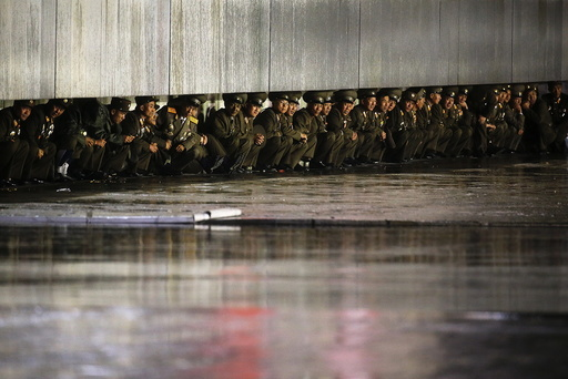 North Korean officers shield themselves from the rain after the parade celebrating the 70th anniversary of the founding of the ruling Workers' Party of Korea, in Pyongyang