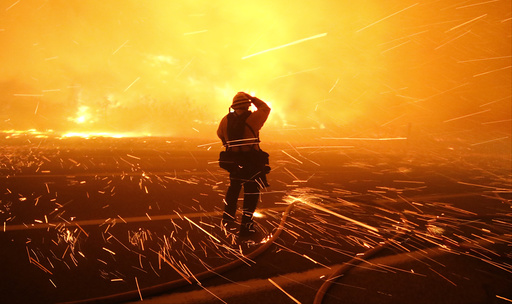 Fire photographer Tod Sudmeier gets hit with flying embers from strong winds at the Solimar brush fire that started early Saturday morning in Ventura County