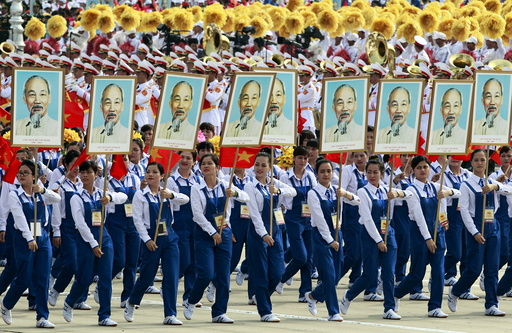 Workers carry portraits of late Vietnamese revolutionary leader Ho Chi Minh during a parade marking their 70th National Day at Ba Dinh square in Hanoi, Vietnam