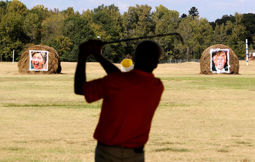Mike Williams, owner of the Alpine Target Golf Center, shows off his swing at a driving range with hay bales covered with the portraits of U.S. presidential nominees Hillary Clinton and Donald Trump
