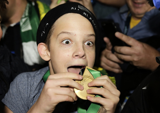 A boy displays the winners' medal given to him by Sonny Bill Williams of New Zealand after the Rugby World Cup Final against Australia at Twickenham in London